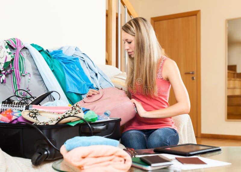 Ropa y accesorios del embalaje de la mujer en la maleta fotografía de archivo libre de regalías