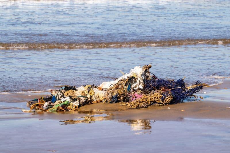 Ropa y desperdicios lavados para arriba sobre la playa de la arena por el Oc?ano Atl?ntico, Agadir, Marruecos fotografía de archivo