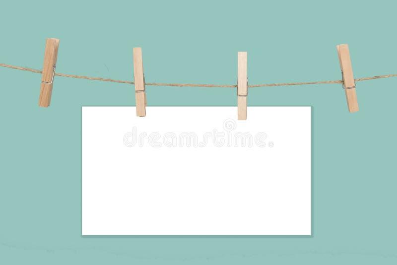 Rope с пустыми рамками белой бумаги с космосом для экземпляра и зажимками для белья на голубой предпосылке стоковое фото rf