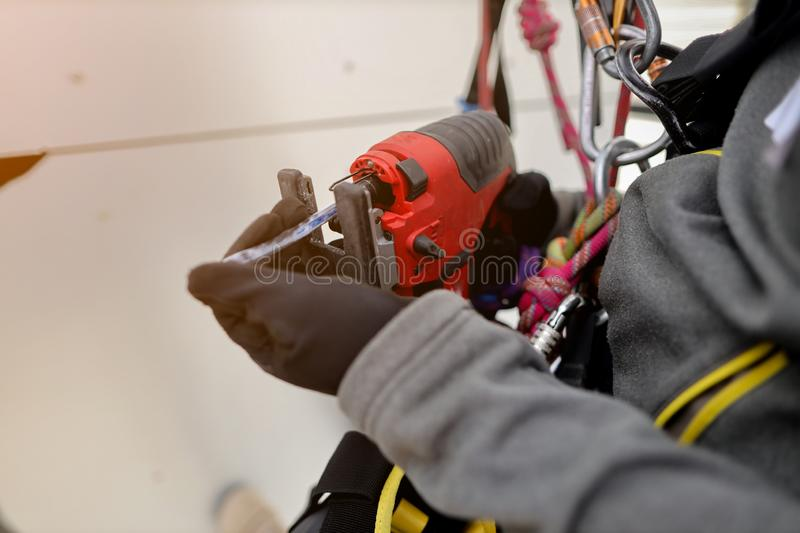 Rope access carpentry abseiler working at height worker wearing a safety hand glove protection inspecting electric hacksaw blade. Prior to used construction royalty free stock photo