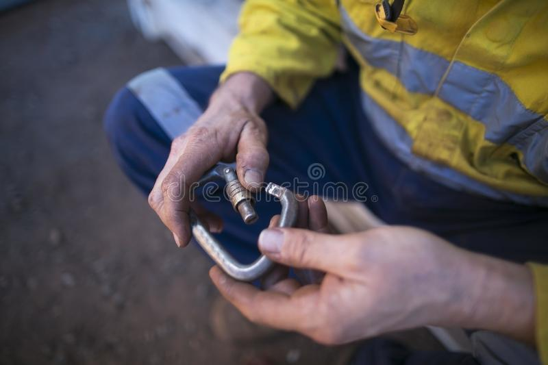 Rope access inspector hand commencing daily safety checking inspecting locking Carabiner defective equipment. Prior to used at construction site Sydney stock photo