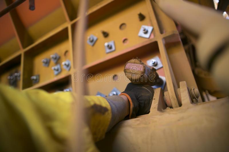 Rope access miner hand wearing a safety glove using battery rattle gun and fastening the bolts on construction site royalty free stock images