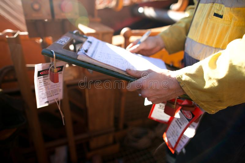Rope access miner supervisor inspecting and checking name list on isolation permit holder box ensure all construction miners are l stock photo