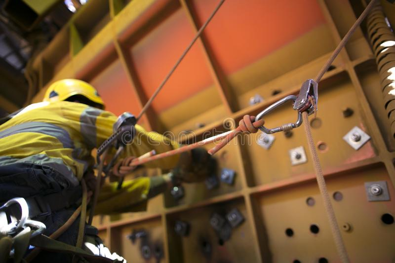 Rope access miner working at height hanging on harness commencing chute repairs which have secondary safety back up device knowing. As caw tail on right hand stock photography