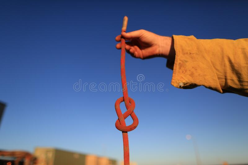 Rope access technician construction mine worker holding static 10.5 mm low stretch rope inspecting a figure of eight knot royalty free stock image