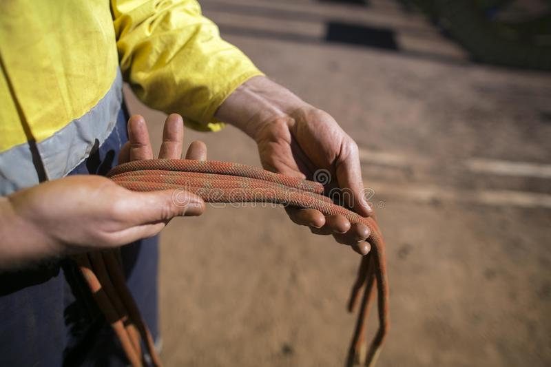 Rope access technician inspector male hand inspecting 10.5 mm low stretch cow tail secondary safety back rope stock photo