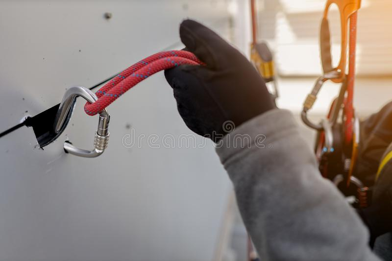 Rope access worker wearing black safety glove checking attachment rope on Karabiner to ensure is safety connecting into panel. Rope access worker wearing black stock image