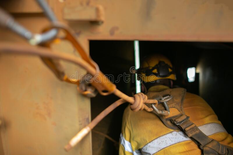 Rope access worker wearing safety harness, helmet connecting three two one rescue pulley system into back of safety harness loop royalty free stock photo
