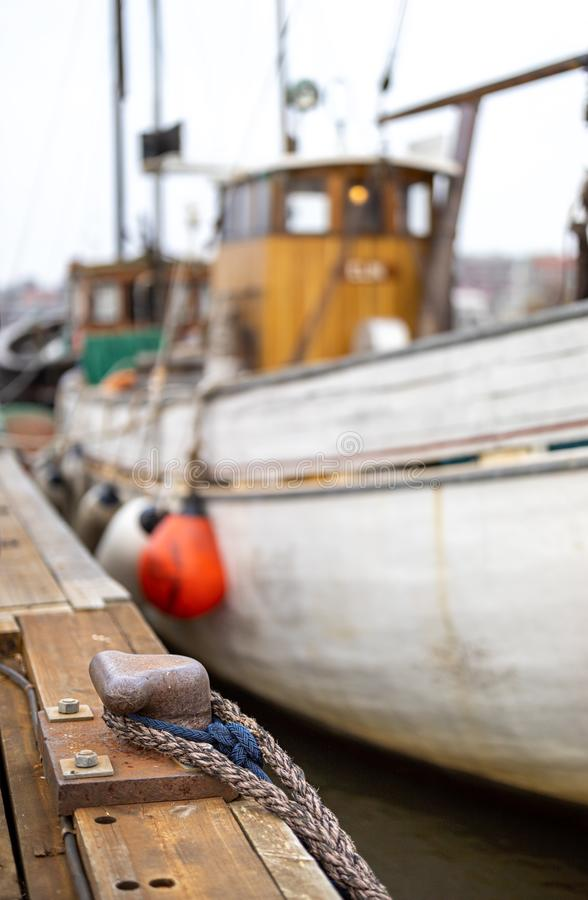 Rope around the bollard and old fisign boat in background blur. Rope around the bollard among various boats on the veteran boat association club at Klippans royalty free stock photos