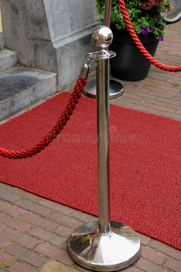Rope barriers on VIP entrance. Big metal poles and red rope barriers on VIP entrance royalty free stock photo