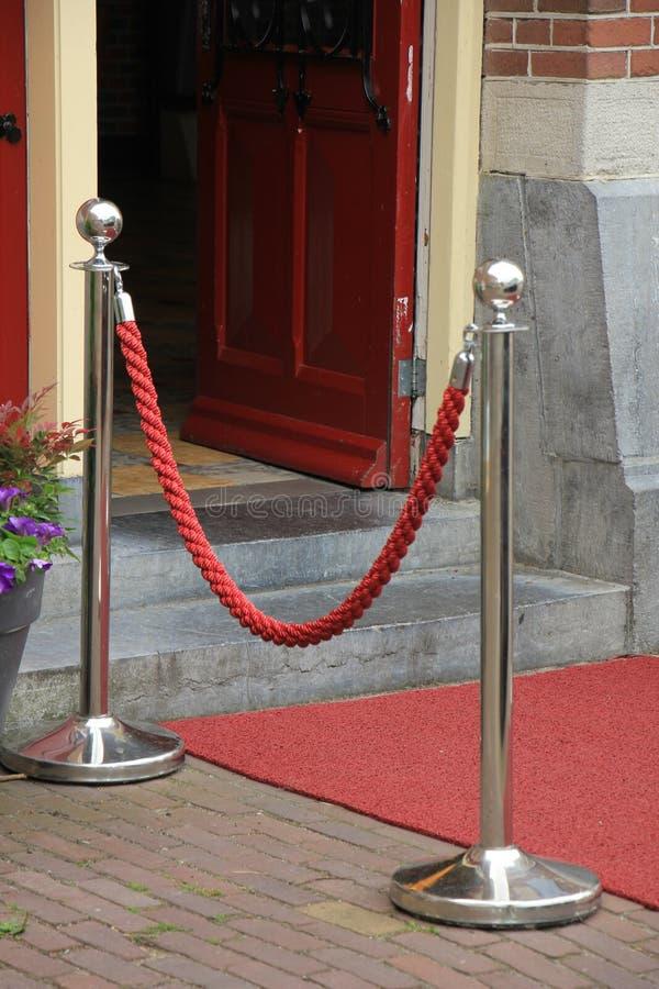 Rope barriers on VIP entrance. Big metal poles and red rope barriers on VIP entrance stock photos