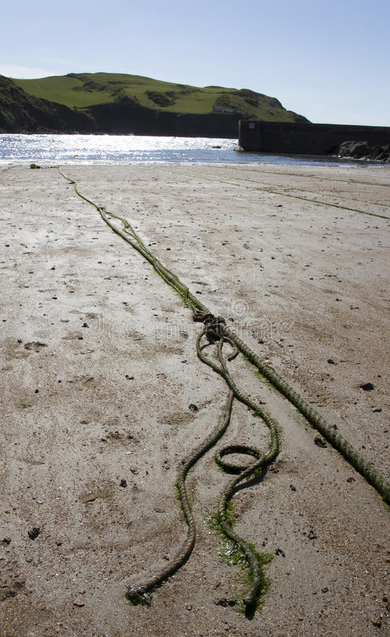 Rope on a beach with sea and hills in the background. Rope on a sunny beach with sea and hills in the background. Quay and headland in background on a beach royalty free stock photo