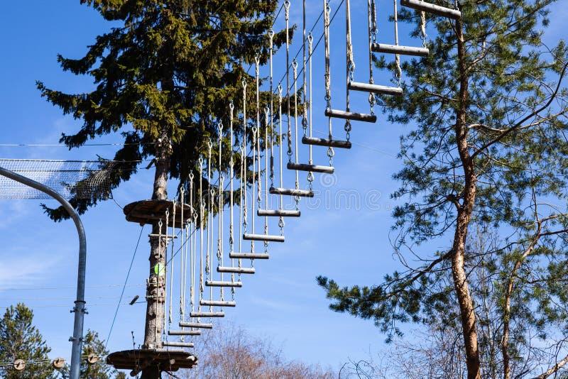 Rope el parque de la aventura en un paisaje esc?nico del cielo azul del bosque del verano Superando obstáculos y alcanzar alturas fotos de archivo