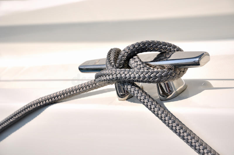 Rope fasten on stake of yacht stock image
