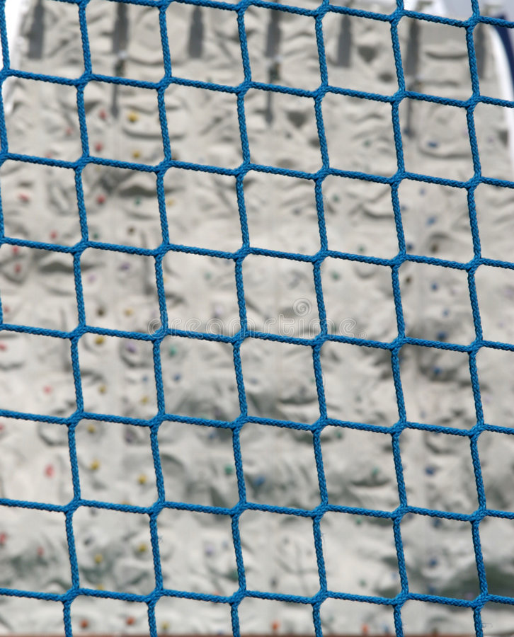 Rope Fence. Blue rope fence with rock climbing wall in background royalty free stock photo