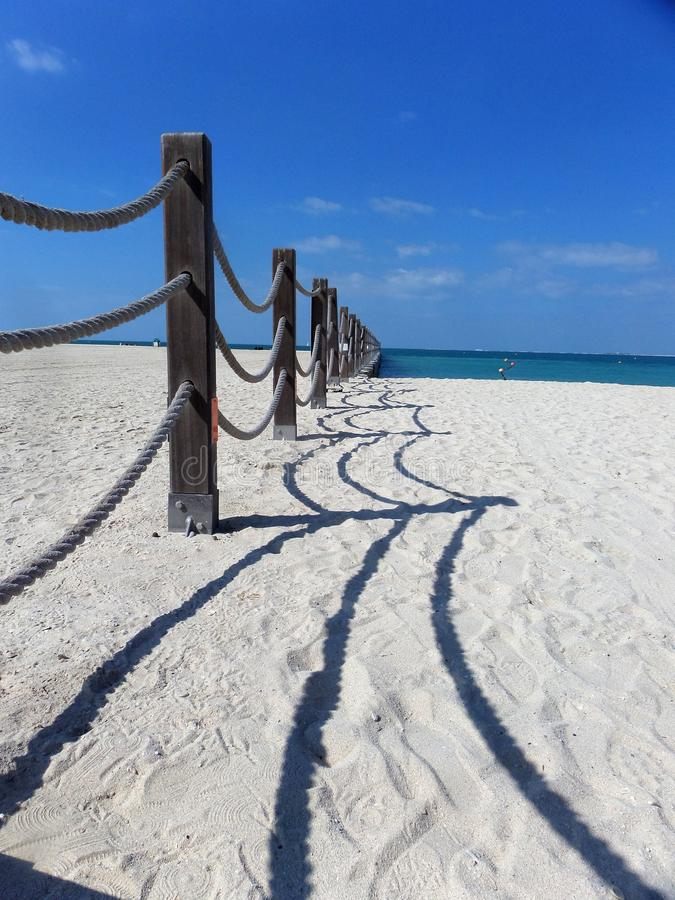 Rope fence and shadow on the beach. Plank footpath and fence boundary rope barrier on the beach royalty free stock photo
