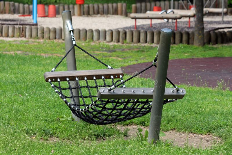Rope hammock swing enforced with strong wooden and metal support made for climbing and relaxing in local public park surrounded royalty free stock photo