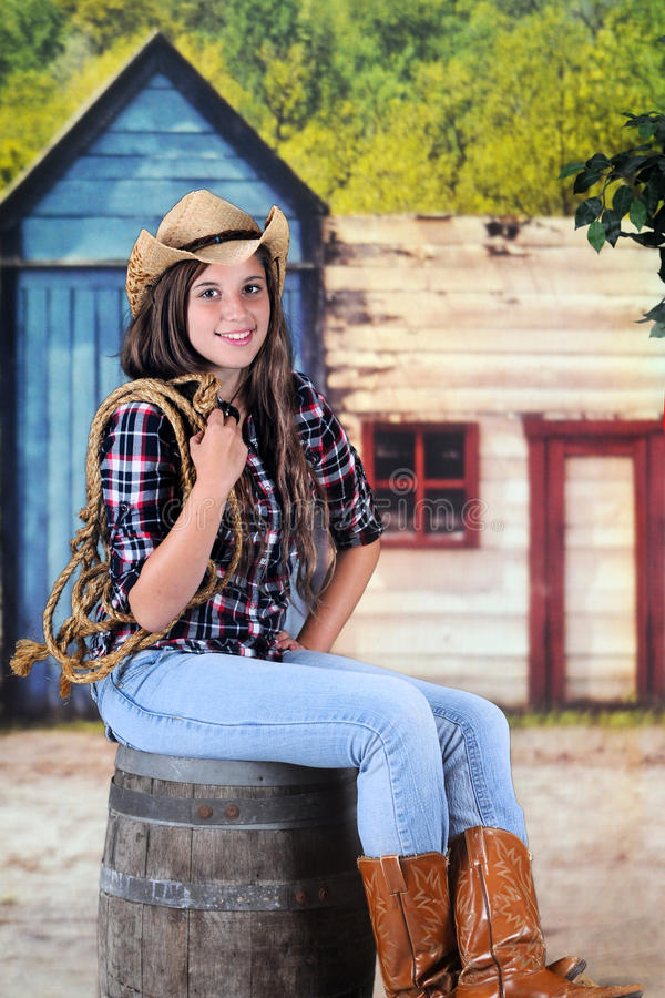 Rope-Holding Cowgirl. A beautiful young teenage cowgir holding a rope while sitting on an old barel in a wild-west town stock image