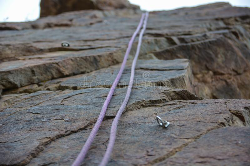 Rope and hook on the rock climbing stock photo