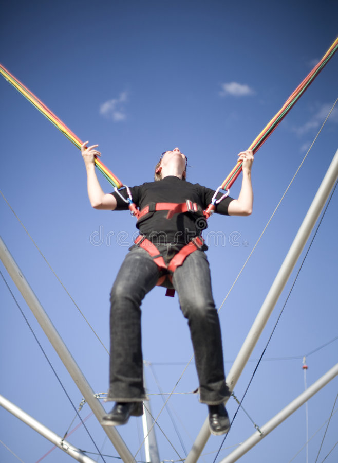 Rope jumper having fun. A woman is in a rope harness where she's jumping up into the sky with her head back laughing stock images