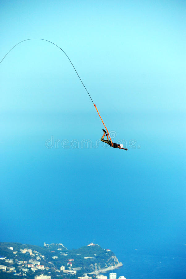Rope jumping. Jump off a cliff with a rope, mountain, sea, nature royalty free stock photos
