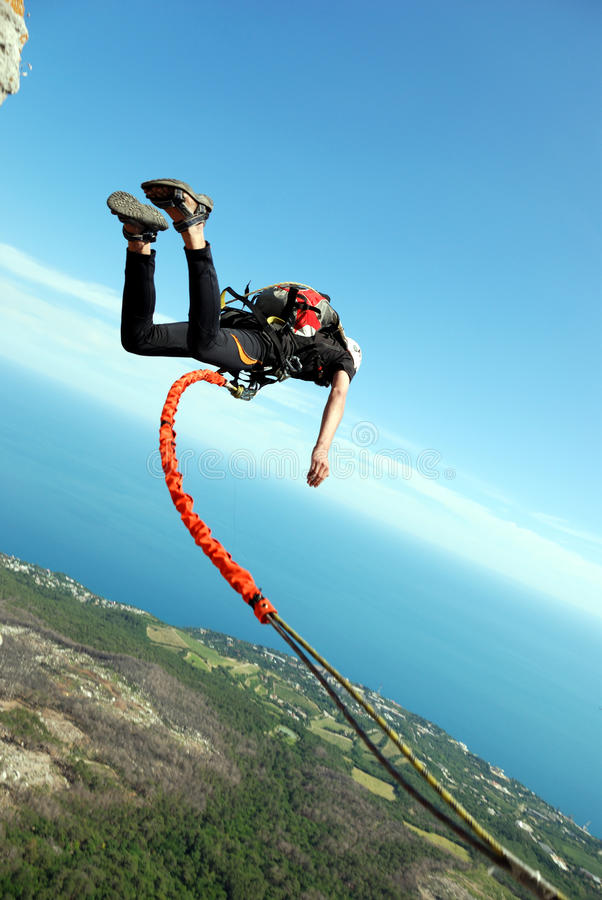 Rope jumping. Jump off a cliff with a rope, mountain, sea, nature stock photo