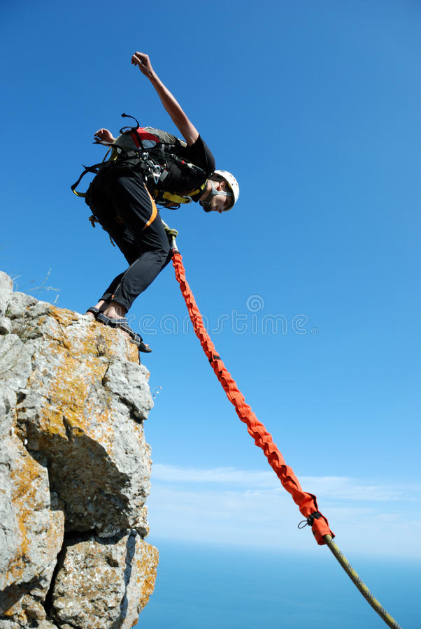 Rope jumping. Jump off a cliff with a rope, mountain, sea, nature stock images