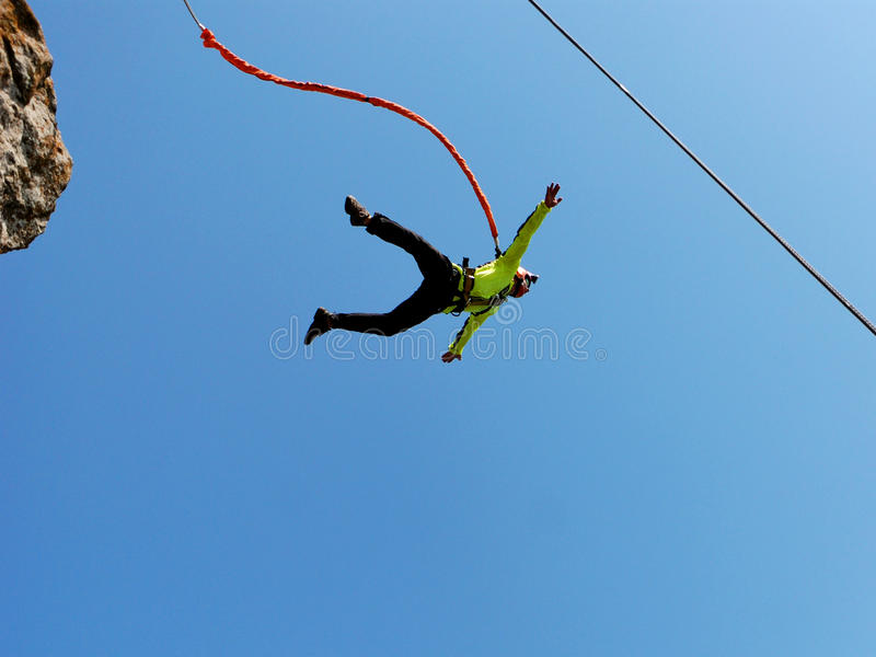 Rope jumping. Jump off a cliff with a rope, mountain, sea, nature royalty free stock photo
