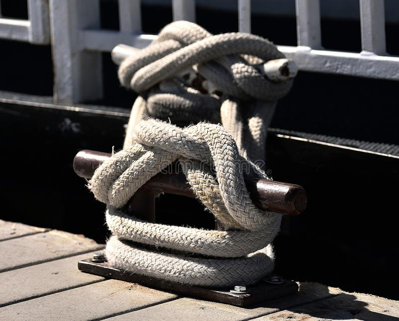 Rope knotted at a pier. With bollard. Rope knotted to a bollard at a wooden pier or wharf stock images