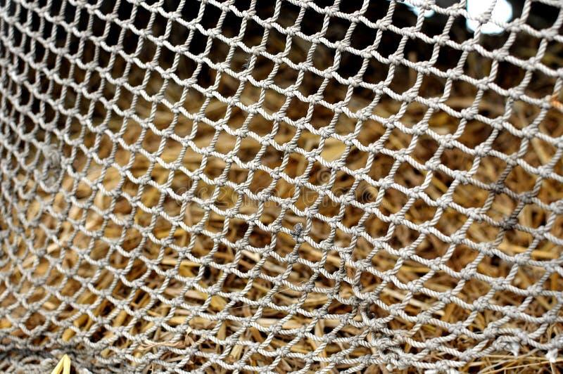 Rope la malla en el fondo borroso de la pila de heno contexto de la textura imagenes de archivo