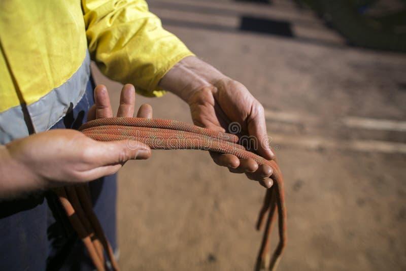 Rope la mano masculina del inspector del técnico del acceso que examina 10 cuerda secundaria de la parte posterior de la segurida foto de archivo
