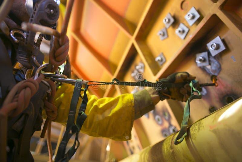 Rope a mão masculina do mineiro do acesso que trabalha no grampeamento de começo da altura que posiciona o gancho da segurança co fotografia de stock royalty free