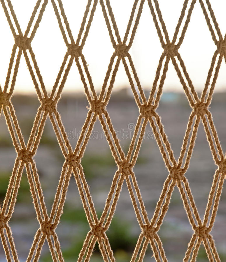 Rope net horizon line texture. Texture of horizon line falling through a hammock style rope chair hanging from the ceiling on a balcony. Generic shot location stock photo