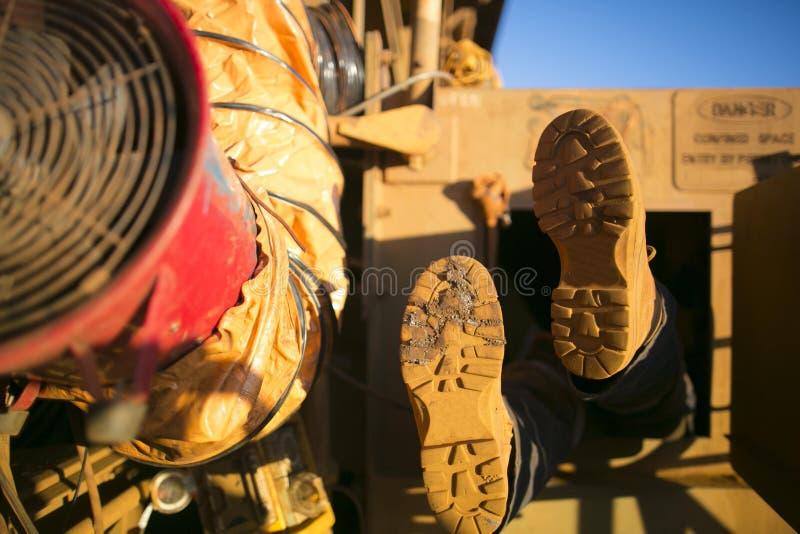 Rope o chicote de fios vestindo da bota da segurança do mineiro do acesso, capacete que participa no espaço limitado fotos de stock