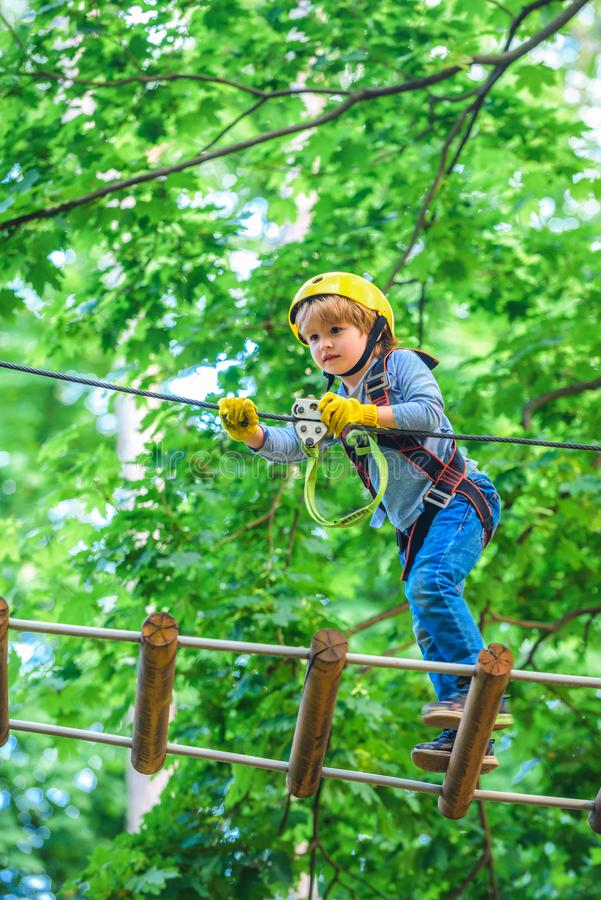 Rope park - climbing center. Carefree childhood. Little child climbing in adventure activity park with helmet and safety. Equipment. Roping park stock image
