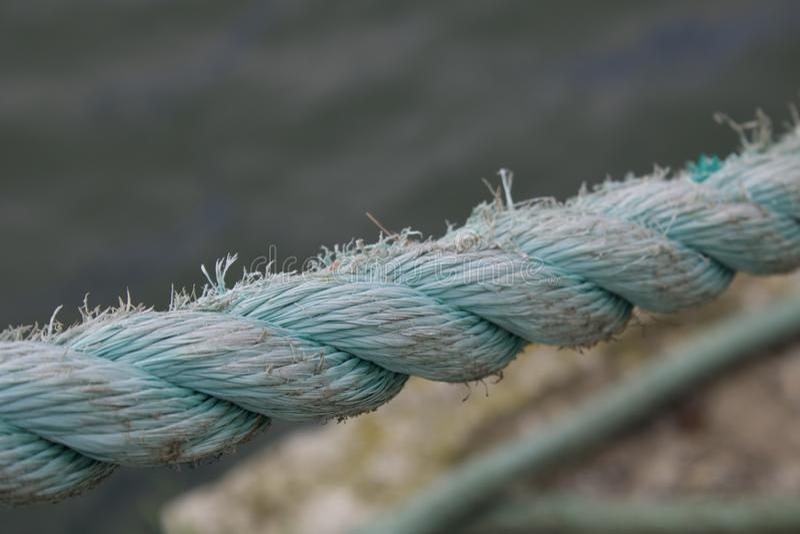 Rope on peer. Blue, strings, water, boat, tie, amarras, corda royalty free stock photos