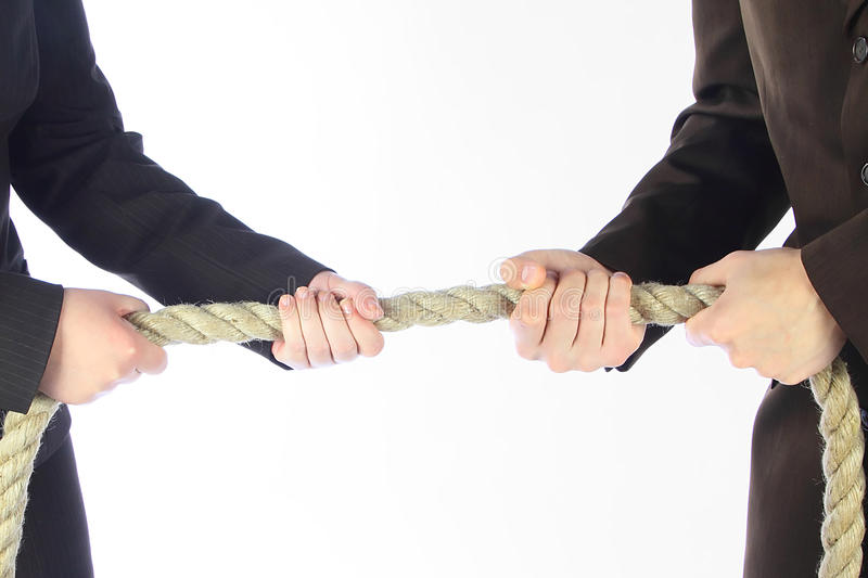 Rope pulling. The men and the women in business suits draw a rope stock photo