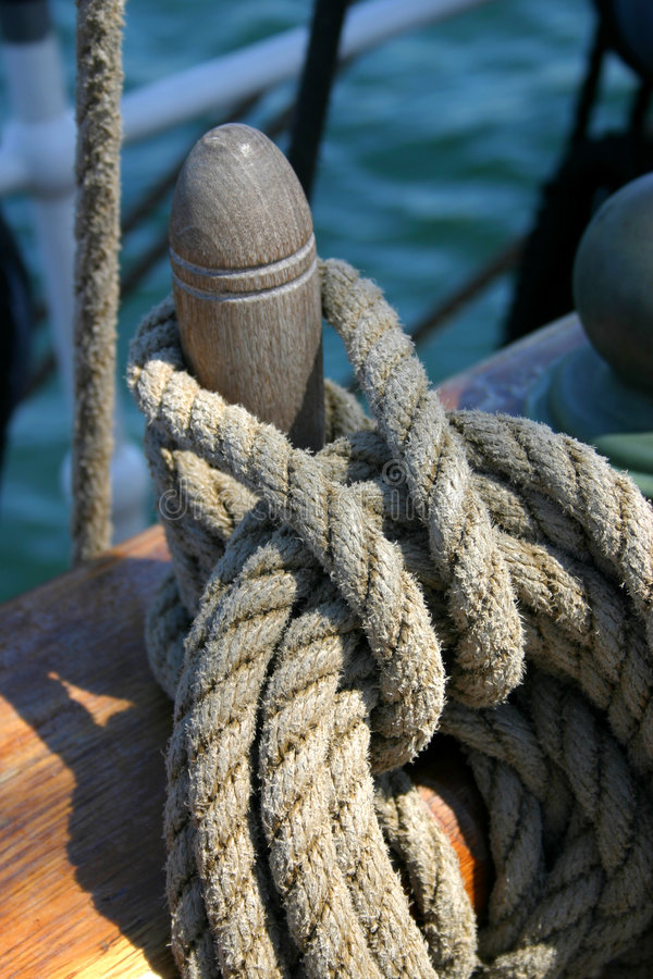 Rope tied around wooden cleat royalty free stock images