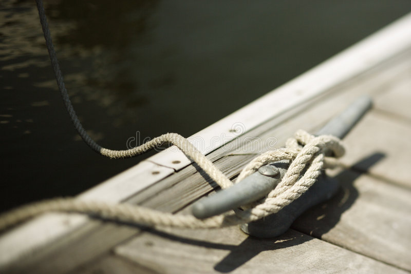 Rope tied to cleat on dock stock photography