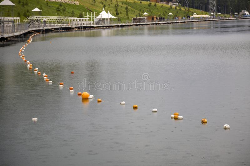 Rope with white and yellow restriction markers on water surface for prohibiting of swimming in deep lake or sea.  stock image