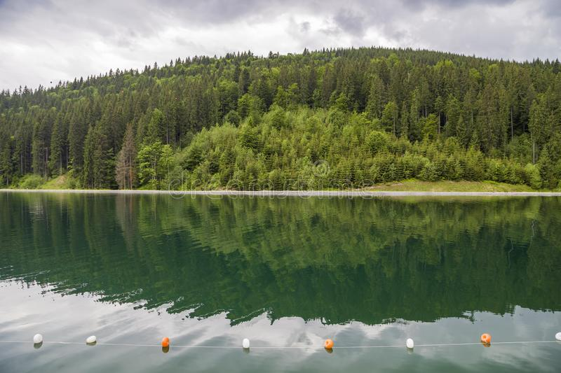 Rope with white and yellow restriction markers on water surface for prohibiting of swimming in deep lake or sea.  stock photo