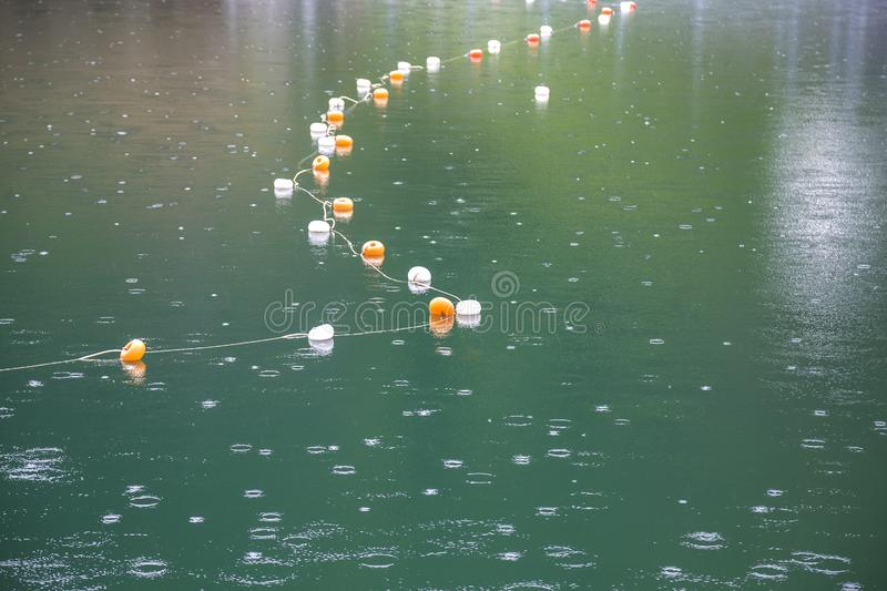 Rope with white and yellow restriction markers on water surface for prohibiting of swimming in deep lake or sea.  royalty free stock photos