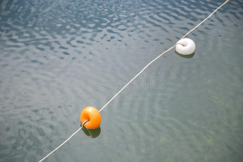 Rope with white and yellow restriction markers on water surface for prohibiting of swimming in deep lake or sea.  royalty free stock photography