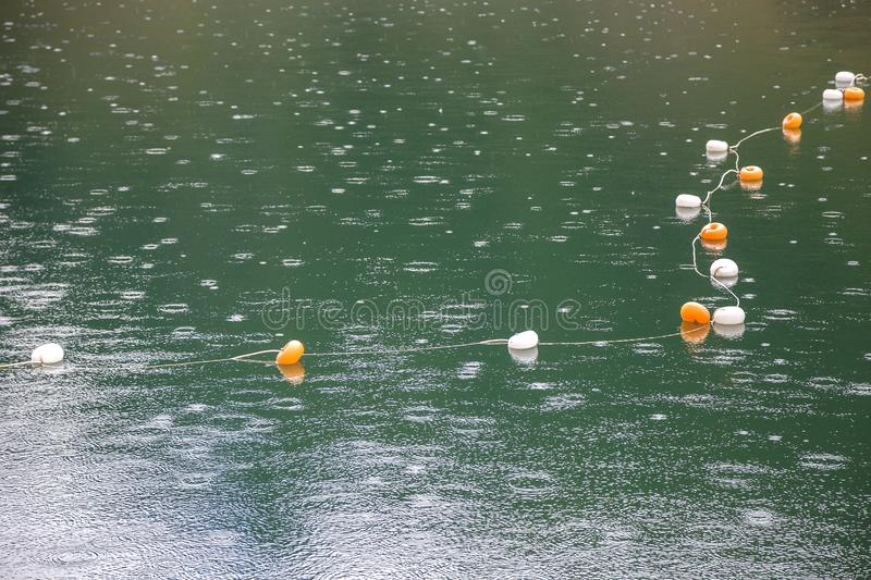 Rope with white and yellow restriction markers on water surface for prohibiting of swimming in deep lake or sea.  stock images