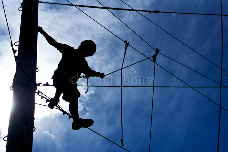 Ropes Course Climber. Young man attempts the ropes course for the first time royalty free stock image