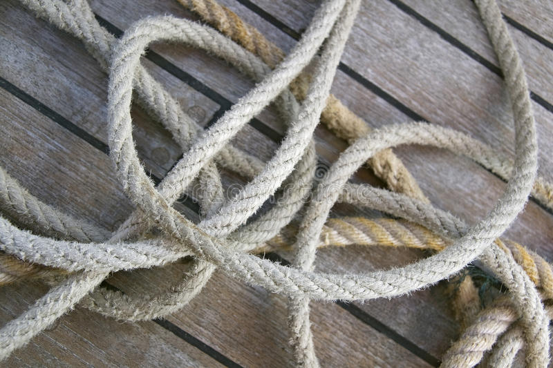 Ropes on a deck. Close-up of thick textile ropes laying on a ship's deck royalty free stock photo