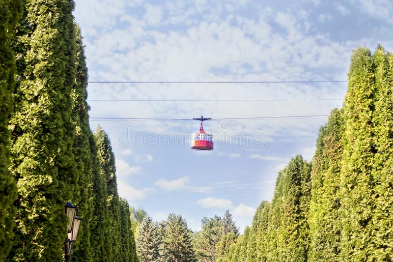 The ropeway and the red. Funicular goes between trees royalty free stock images