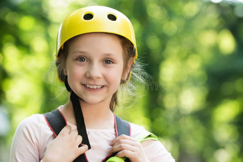 Roping park. Happy little girl climbing in the trees. Teenager girl adventure and travel. Beautiful Little girl climbing stock photography