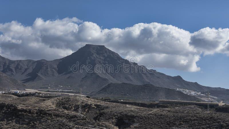 Roque del Conde com sua cimeira lisa, sob a luz solar bonita da manhã, vistas da vila pequena elegante do La Caleta, Te imagens de stock