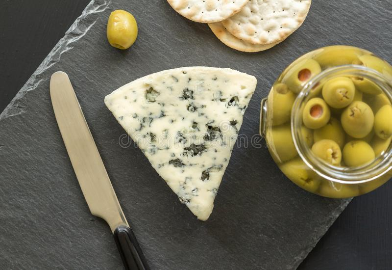 Roquefort cheese wedge top view photo with crackers and green olives stock photo